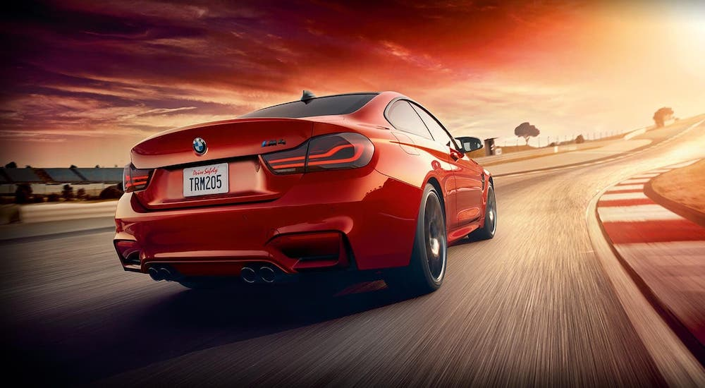 A red 2020 BMW M4 coupe is shown from the rear on a racetrack.