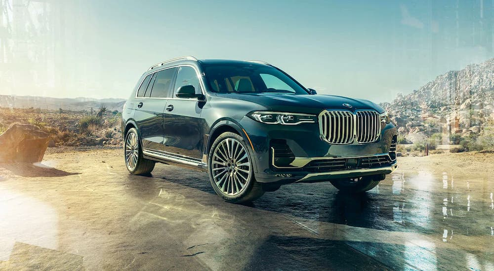 A blue/gray 2020 BMW X7 is parked in a desert.