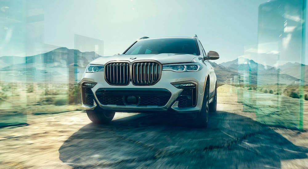 A white 2020 BMW X7 is driving in a desert far from Cincinnati, OH, shown from the front.