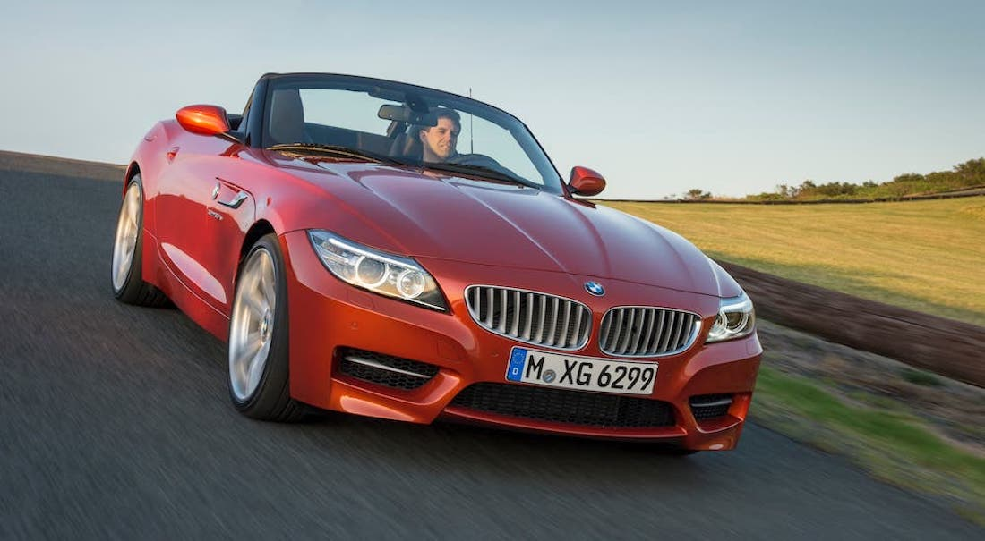 What might as well be a BMW sports car, a red 2021 BMW Z4 convertible, is shown driving past a field near Cincinnati, OH.