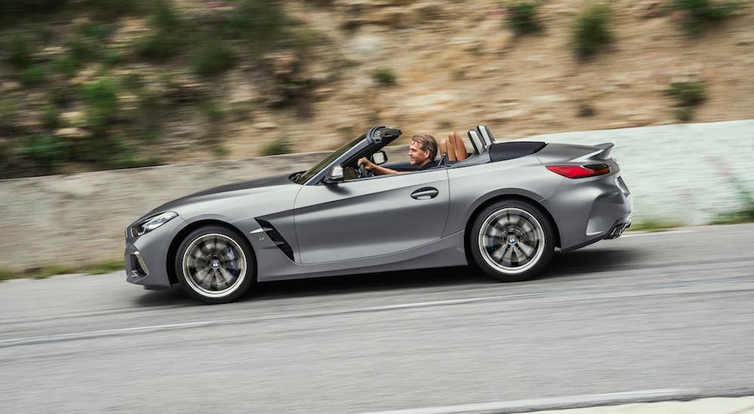 A silver 2021 BMW Z4 is shown from the side driving on a highway.