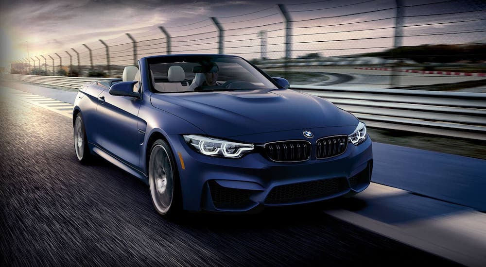 A blue 2021 BMW M5 Convertible is driving on a racetrack.
