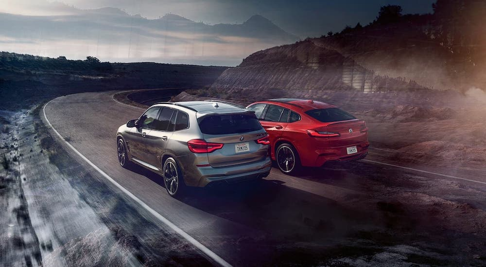 Two vehicles from the BMW M Series, a silver 2021 X3 M and a red X4 M, are shown from the rear driving around a winding road.