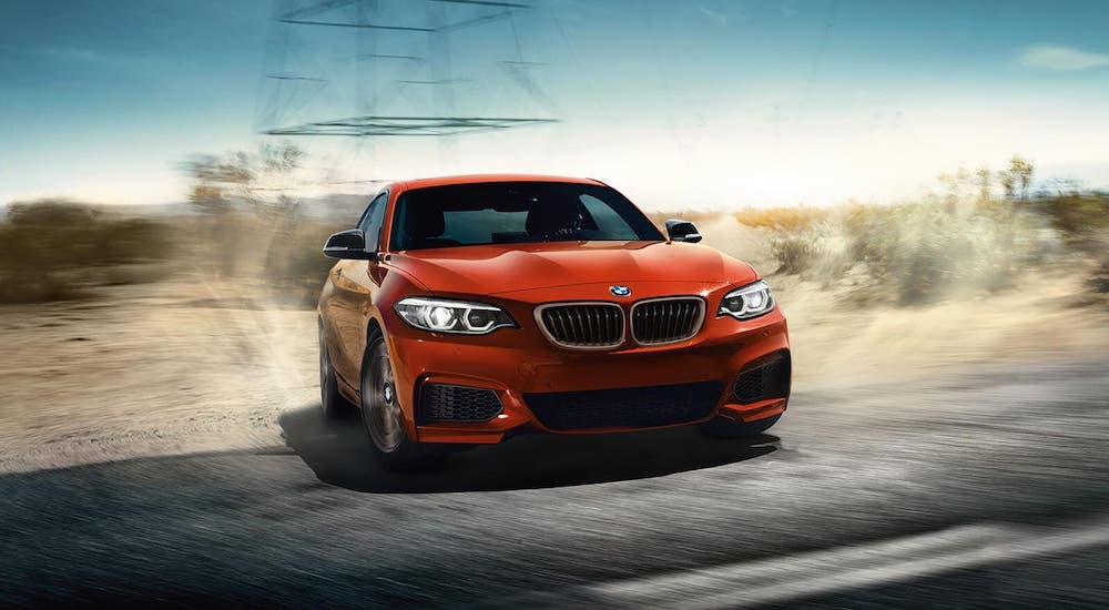 A popular BMW sports car, an orange 2020 BMW 2 Series sedan, is driving from a dirt road onto pavement.