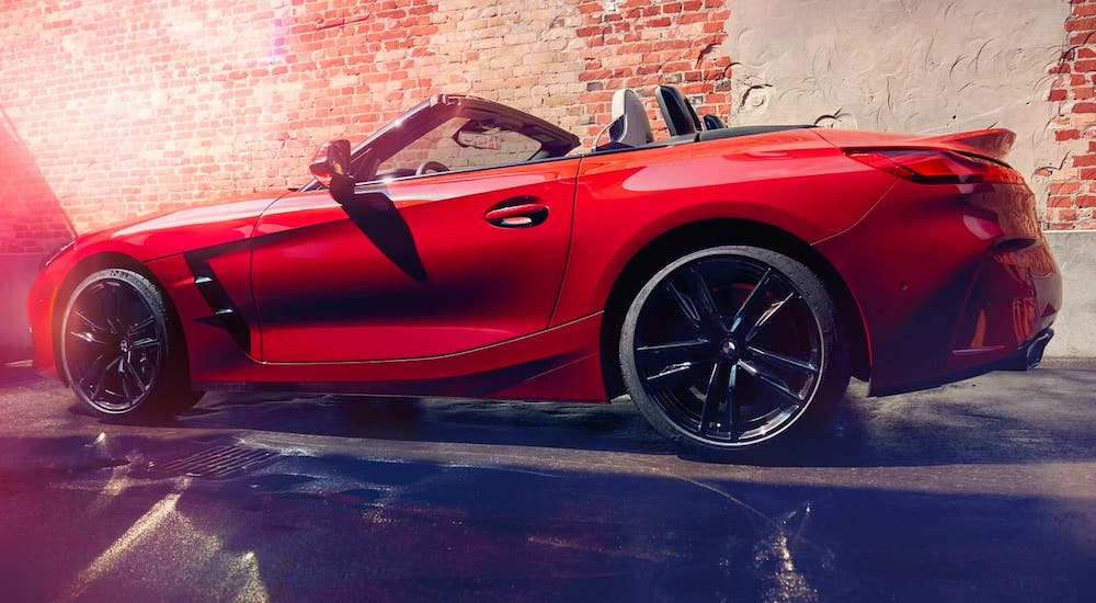 A red 2020 BMW Z4 Roadster convertible is shown from the side in front of a brick wall.