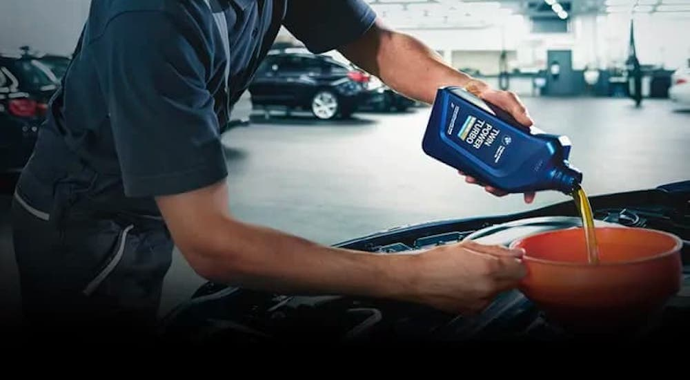 A mechanic is pouring oil into an engine as part of a BMW service near you.