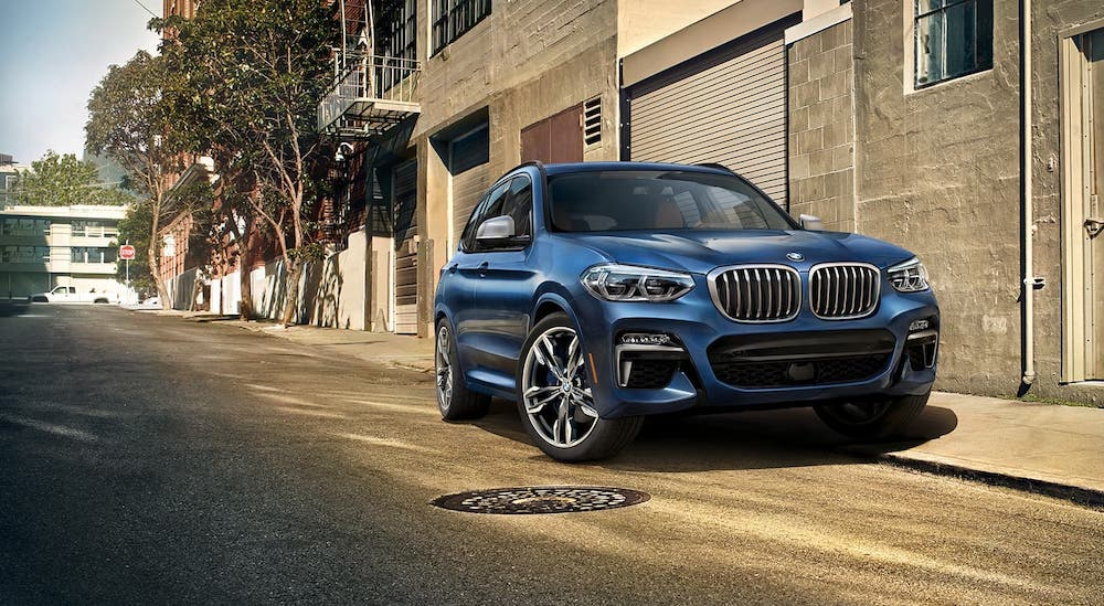 A blue 2017 BMW X3 is parked on a city street.
