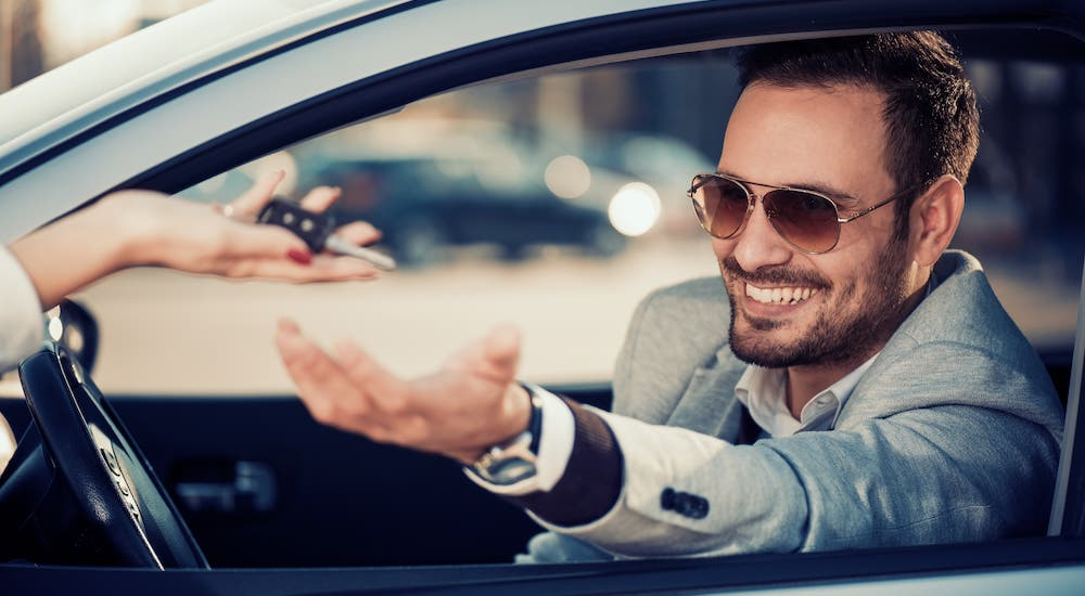A smiling man is sitting in a pale blue car is holding out his hand and being handed car keys.