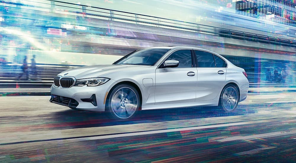 A white 2019 BMW 3 Series is driving around a race track.