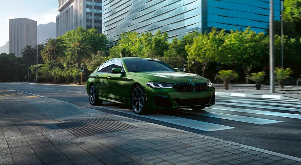 A newer used BMW near you, a green 2019 BMW 5 Series, is parked on a city street.